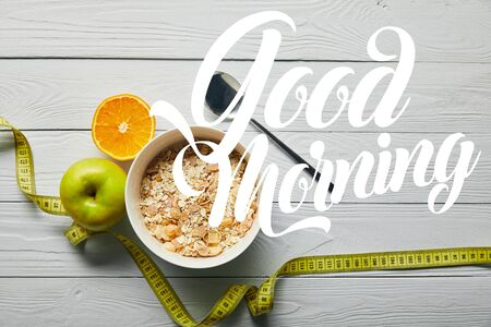 top view of measuring tape, spoon and breakfast cereal in bowl near apple and orange on wooden white background with good morning lettering
