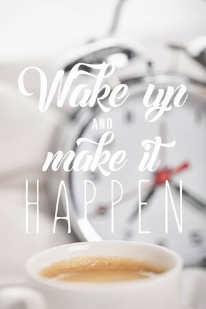 selective focus of coffee in white cup with silver alarm clock in bed on background with wake up and make it happen Фото со стока