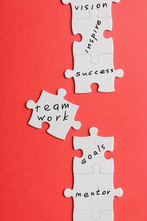 top view of white connected jigsaw near puzzle piece with words isolated on red Stok Fotoğraf