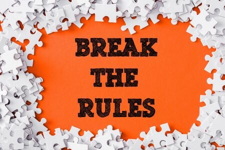 top view of frame of white jigsaw puzzle pieces around break the rules lettering on orange 写真素材