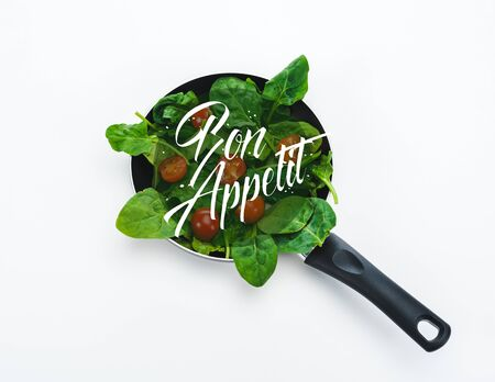fresh spinach leaves and cherry tomatoes in frying pan with bon appetit lettering on white background Imagens