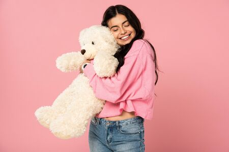 smiling young woman hugging teddy bear, Isolated On pink