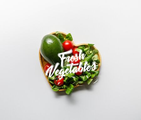 top view of fresh green vegetables in heart shaped bowl on white background with fresh vegetables lettering