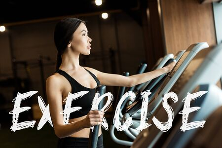 selective focus of attractive woman in sportswear working out on exercising bike  with exercise illustration