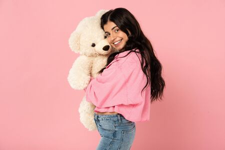 smiling girl hugging teddy bear, Isolated On pink