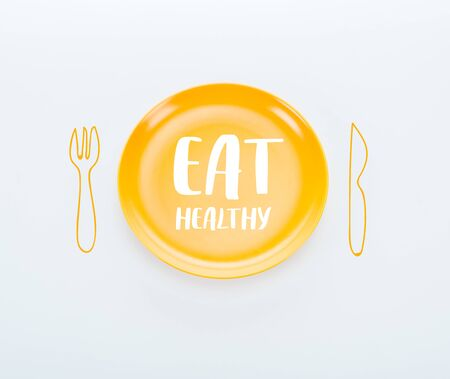 top view of shiny yellow plate with eat healthy lettering and cutlery illustration on white background
