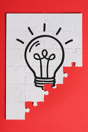 top view of white connected puzzle pieces with light bulb isolated on red