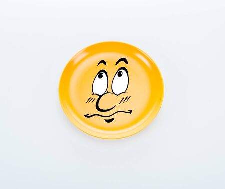 top view of shiny yellow plate with sad smiley on white background Stockfoto