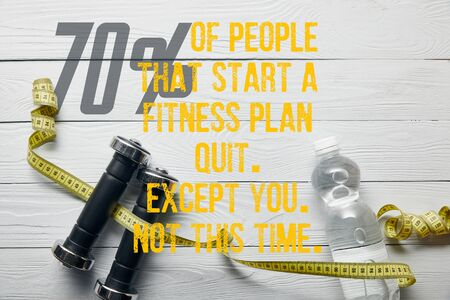 top view of bottle with water, measuring tape and dumbbells on wooden white background with 70% of people that start a fitness plan quit, except you, not this time illustration