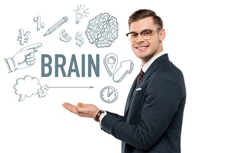 happy businessman in glasses gesturing and smiling near brain lettering on white Stock Photo