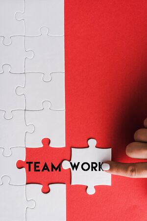 top view of woman pointing with finger at jigsaw near connected puzzle pieces with teamwork lettering on red