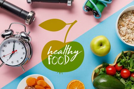 top view of delicious diet food and sport equipment with alarm clock on blue and pink background with healthy food lettering