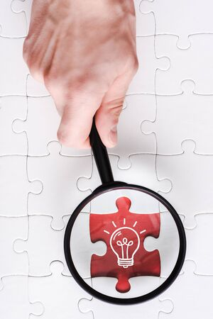 top view of man holding magnifying glass near jigsaw with light bulb near white connected puzzle pieces 写真素材