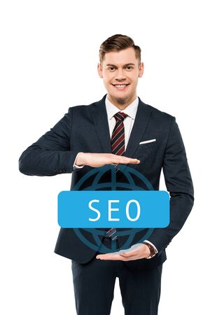 cheerful businessman gesturing near seo lettering and looking at camera on white