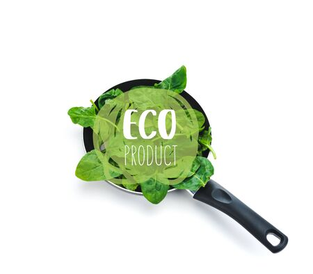 green fresh spinach leaves in frying pan with eco product lettering on white background