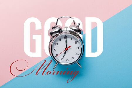 top view of classic silver alarm clock on pink and blue background with good morning lettering