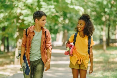 two smiling multicultural schoolkids walking in park while holding skateboards Banque d'images