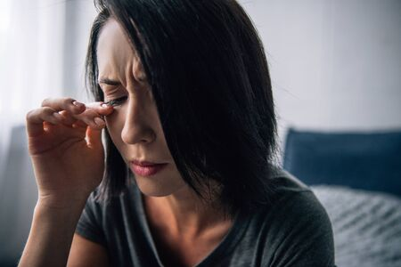 beautiful depressed woman crying and wiping tears at home Stock Photo