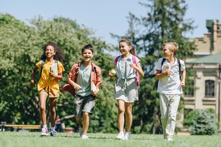 four happy multicultural schoolchildren running on lawn in park together