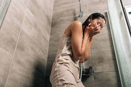 depressed woman covering face with hands while crying in shower at home