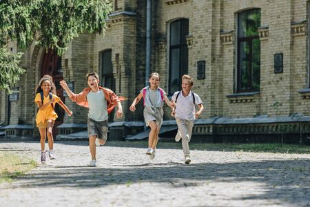 four adorable multicultural schoolchildren smiling while running in schoolyard 写真素材 - 131900867