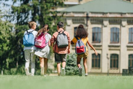 back view of four multicultural schoolkids with backpacks walking on lawn in park 写真素材 - 131901275