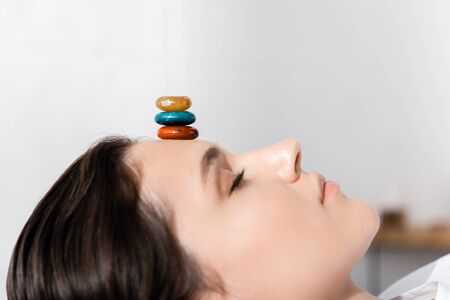 woman lying with closed eyes with colorful stones on forehead