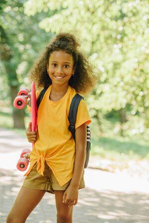 adorable african american schoolgirl smiling at camera while holding skateboard Reklamní fotografie