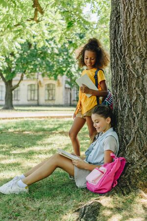 adorable african american schoolgirl standing near friend sitting on lawn under tree and reading book