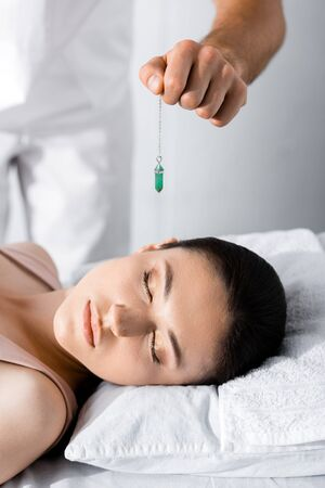 cropped view of hypnotist standing near woman on pillow and holding green stone