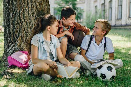 Tres escolares alegres hablando mientras está sentado en el césped bajo el árbol