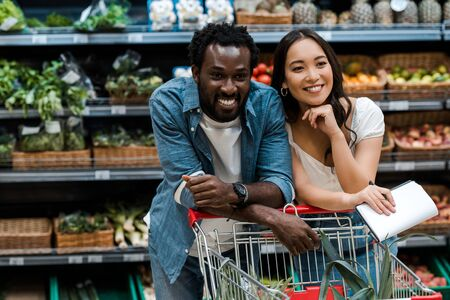 cheerful interracial couple smiling in supermarket near shopping cart 스톡 콘텐츠