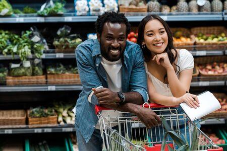 wesoła para międzyrasowa uśmiechająca się w supermarkecie w pobliżu koszyka Zdjęcie Seryjne