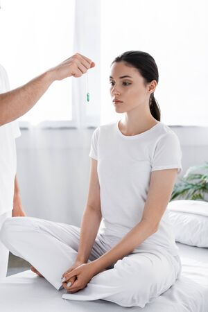 cropped view of hypnotist standing near woman and holding green stone near her face Stock Photo