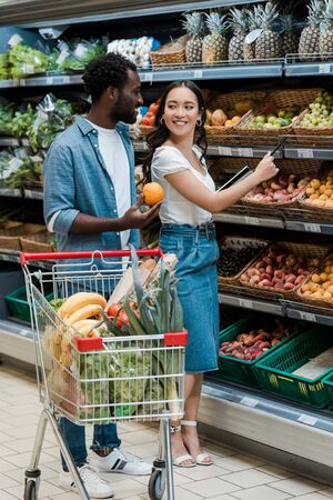 happy african american man looking at asian woman standing in supermarket near fruits Stock Photo