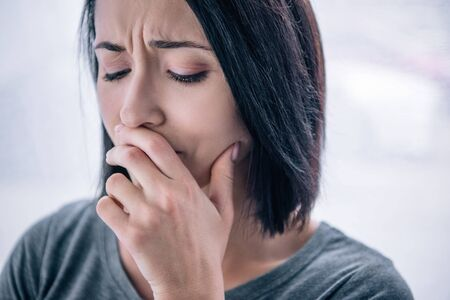beautiful sad woman covering mouth at home Stock Photo