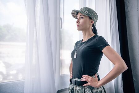 beautiful woman with hand on hip in military uniform at home with copy space
