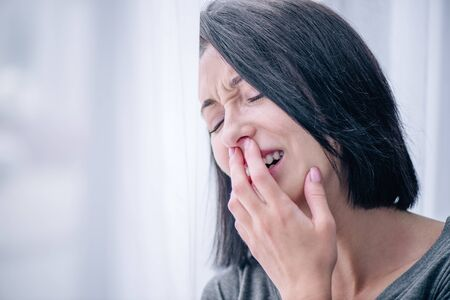selective focus of depressed brunette woman covering mouth and crying at home