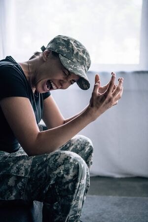depressed woman in military uniform sitting on couch and screaming at home