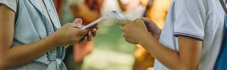 partial view of schoolboy and schoolgirl using smartphones, panoramic shot