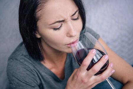 lonely upset woman drinking wine at home
