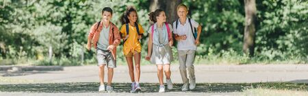 panoramic shot of four happy multicultural schoolkids running in sunny park 写真素材 - 131901191