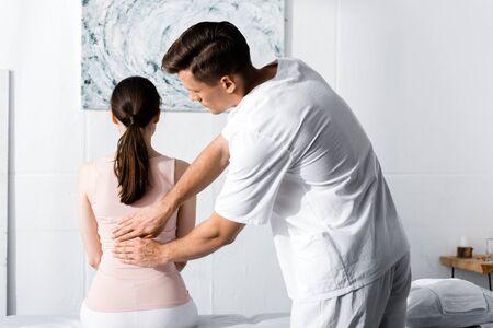 Rückansicht einer Frau, die auf einem Massagetisch sitzt, während der Heiler ihre Aura reinigt