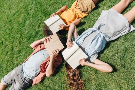 top view of three multicultural schoolkids lying on lawn and covering faces with books 写真素材 - 131901252
