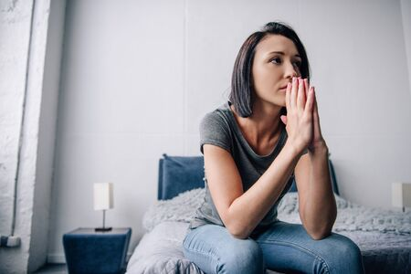 beautiful depressed woman sitting on bed and covering mouth at home