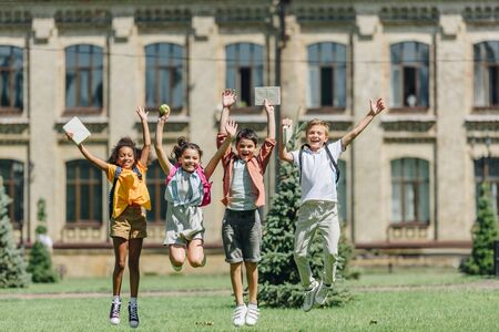 four happy multicultural schoolkids jumping while holding books on lawn in park