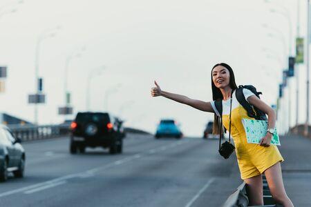schöne und asiatische Frau in gelben Overalls, die per Anhalter unterwegs ist und Karte hält Standard-Bild