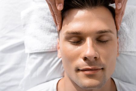 cropped view of masseur standing near man with closed eyes and touching his head