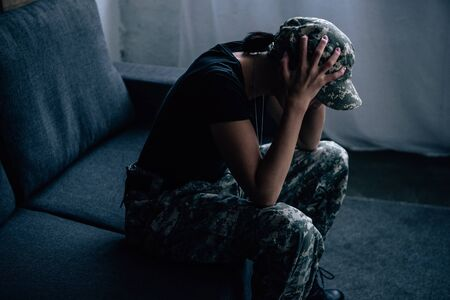 depressed woman in military uniform with hands on head at home
