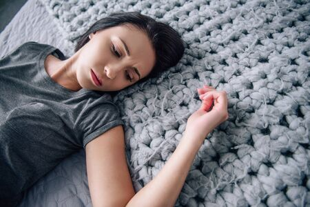 beautiful upset lonely woman lying on bed at home Stock Photo